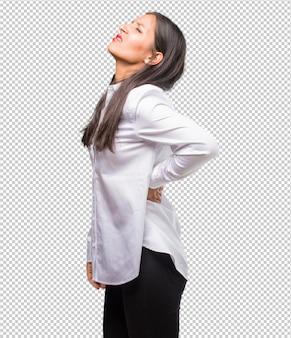 仕事のストレス、疲れ、抜け目がないため背中の痛みを持つ若いインド人女性の肖像画