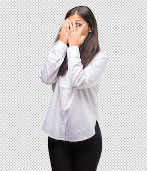 Портрет молодой индийской женщины чувствует себя обеспокоенным и испуганным, смотрит и закрывает лицо, понятие страха и тревоги