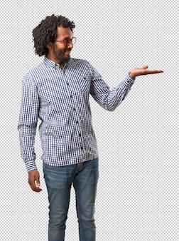 Красивый афро-американский бизнесмен, что-то держит в руках, показывая продукт, улыбаясь и веселый, предлагая воображаемый объект