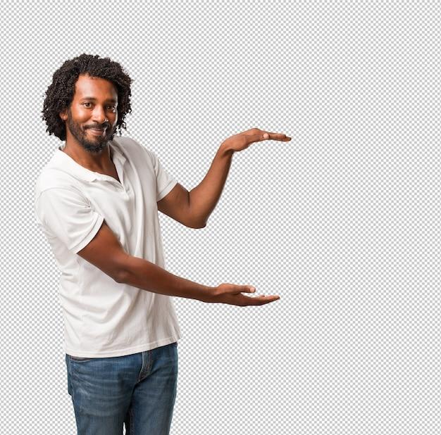 Красивый афроамериканец что-то держит в руках, показывая продукт, улыбаясь и веселый, предлагая воображаемый объект