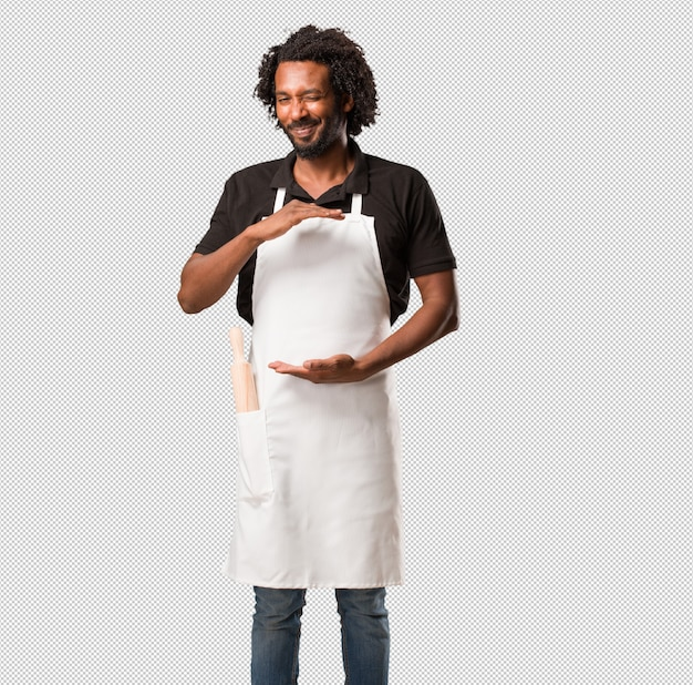 Красивый афро-американский пекарь держит что-то с руками, показывая продукт, улыбаясь и веселый, предлагая воображаемый объект