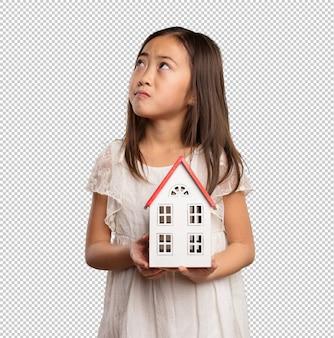 小さな家を保持している中国の少女