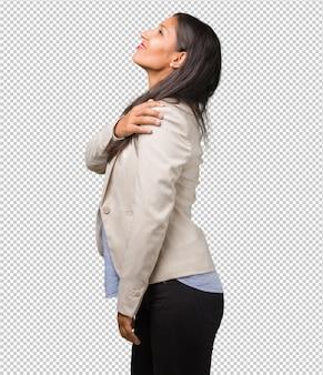 仕事のストレス、疲れ、抜け目がないため背中の痛みを持つ若いビジネスインドの女性