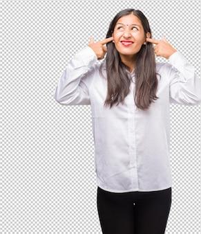 怒って、いくつかの音を聞くのにうんざりの手で耳を覆う若いインド人女性の肖像画