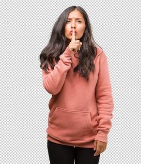秘密を保つか沈黙を求めるフィットネス若いインド人女性の肖像画