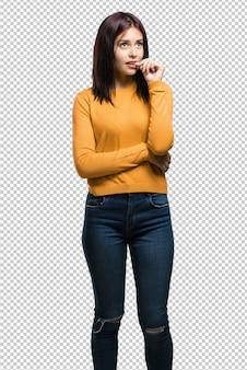 Молодая симпатичная женщина, кусающая ногти, нервная и очень взволнованная
