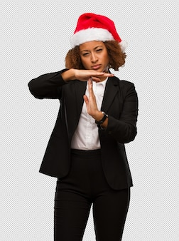 Молодой черный бизнесмен, носить шляпу рождества санта, делая жест тайм-аут