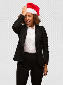 Молодой черный бизнесмен носить шляпу рождества санта забывчивый, реализовать что-то