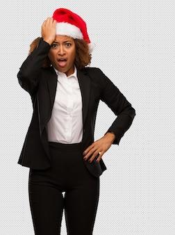 Молодой черный бизнесмен, одетый в рождественскую шляпу санта обеспокоены и перегружены