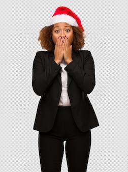 Молодой черный бизнесмен, одетый в рождественскую шляпу санта очень страшно и страшно скрывается