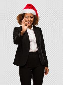 Молодой черный бизнесмен, носить шляпу рождества санта весело и уверенно делать хорошо жест