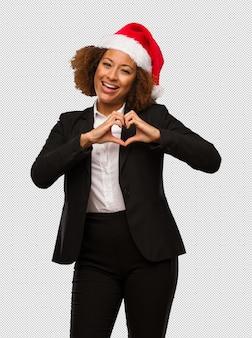 Молодой черный бизнесмен, носить шляпу рождества санта, делая форму сердца с руками