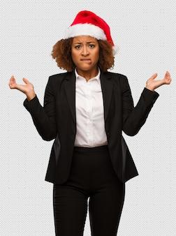Молодой черный бизнесмен носить рождественские санта шляпу запутался и сомнительно