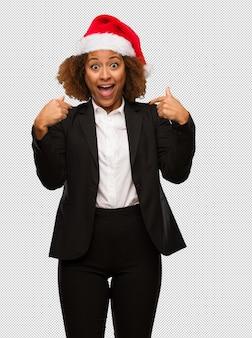 Молодой черный бизнесмен, одетый в рождественскую шляпу санта удивлен, чувствует себя успешным и процветающим