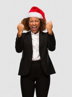 Молодой черный бизнесмен, носить шляпу рождества санта кричать очень сердитый и агрессивный
