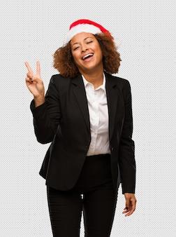 Молодой черный бизнесмен, носить шляпу рождества санта делает жест победы