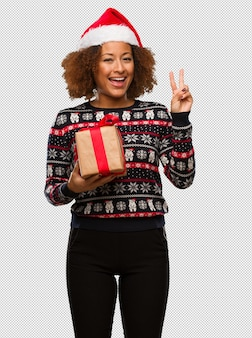 Молодая черная женщина с подарком в день рождества весело и счастливым, делая жест победы