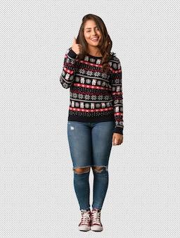 Полная молодая женщина, носить рождественские джерси, улыбаясь и подняв пальца вверх
