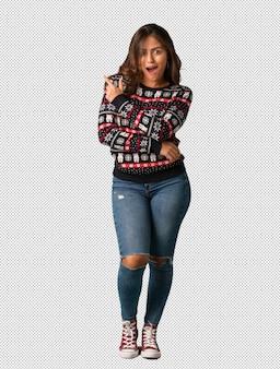 Полная молодая женщина, носить рождественские трикотаж, указывая на сторону