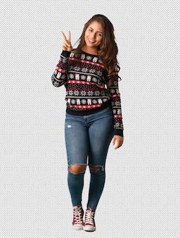 Полная молодая женщина, носить рождественский трикотаж, показывая номер два