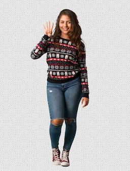 Полная молодая женщина, носить рождественские трикотаж, показывая номер четыре
