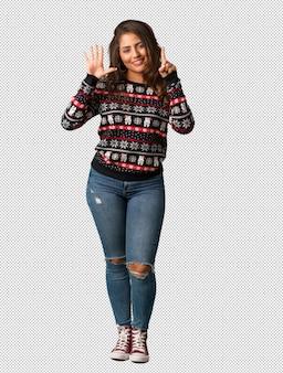 Полная молодая женщина, одетые в рождественский трикотаж с номером шесть