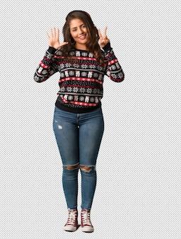 Полная молодая женщина в ношении рождественский трикотаж с номером семь