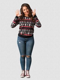 Полное тело молодой женщины, носить рождественские трикотаж, показывая номер восемь