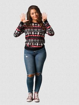 Полное тело молодой женщины, носить рождественские трикотаж, показывая номер девять