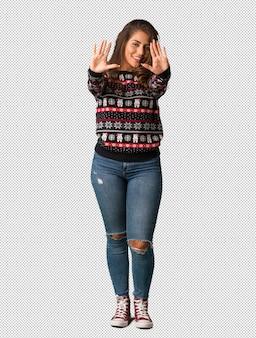 Полная молодая женщина в ношении рождественский трикотаж с номером десять
