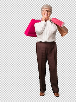 陽気で笑っている全身のシニア女性、ショッピングバッグを持っていることはとても興奮しています