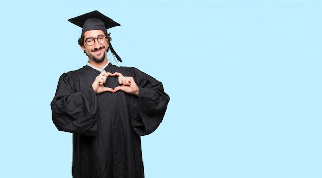 若い、卒業した男がカメラに戻って、腕を交差して立って、物体に向かって