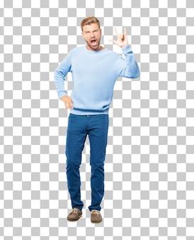 ヤングブロンドの男、ロックを歌って、踊り、叫び、反抗的で怒っている姿勢で体を動かす。