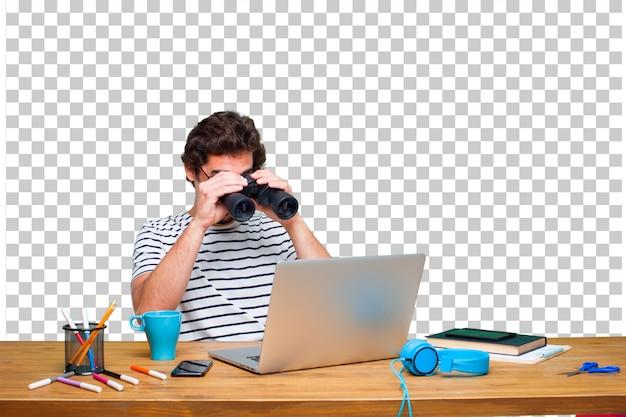 Молодой сумасшедший графический дизайнер на столе с ноутбуком и в бинокль