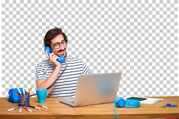 Молодой сумасшедший графический дизайнер на столе с ноутбуком и старинным телефоном