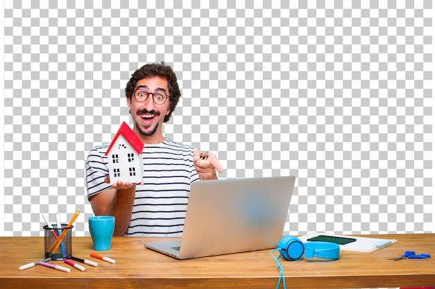 Молодой безумный графический дизайнер на столе с ноутбуком и с моделью дома