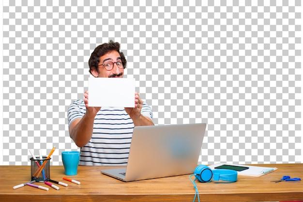 ノートパソコンとプラカードを机の上の若いクレイジーグラフィックデザイナー