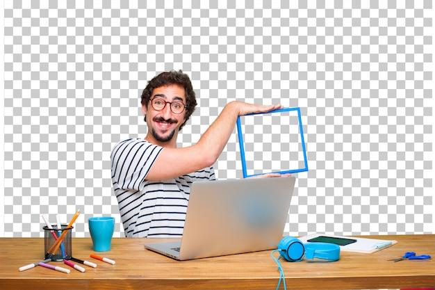 ノートパソコンとフレームを机の上の若いクレイジーグラフィックデザイナー