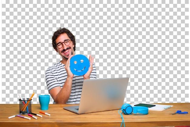 Молодой сумасшедший графический дизайнер на столе с ноутбуком и смайликом смайлик