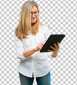 タッチスクリーンタブレットを持つシニアの美しい女性