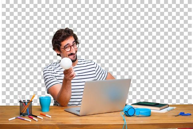 Молодой сумасшедший графический дизайнер на столе с ноутбуком и с лампочкой. идея концепции