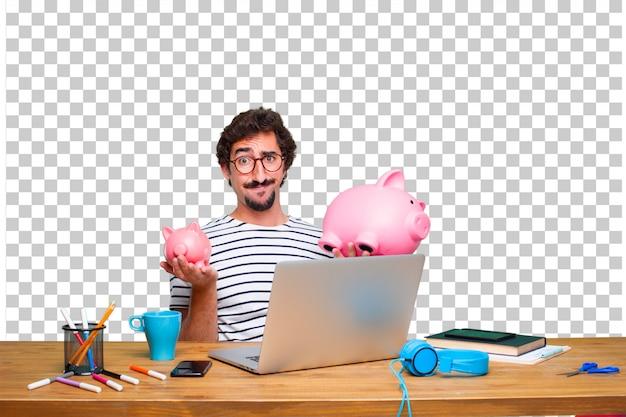 Молодой сумасшедший графический дизайнер на столе с ноутбуком и с копилкой