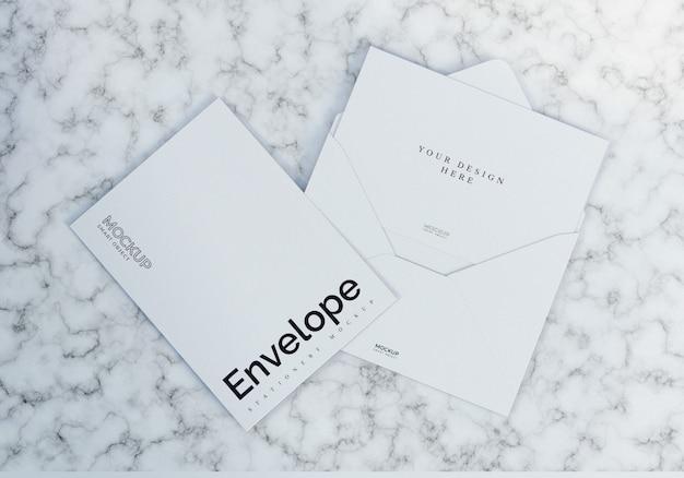 大理石のテクスチャ背景を持つきれいな白い封筒モックアップ