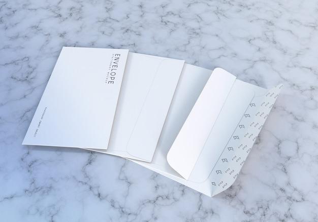 大理石のテクスチャ背景を持つ文房具封筒モックアップデザインテンプレート