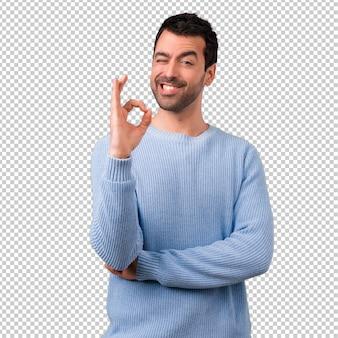Красивый мужчина показывает знак с пальцами