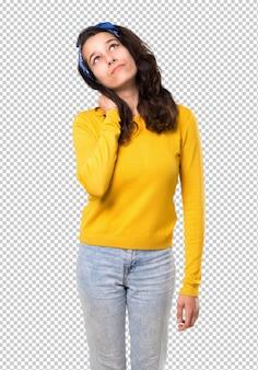 Молодая девушка с желтым свитером и голубой бандана на голове стоя и мышления