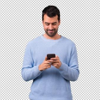 携帯電話を使った青いセーターを持つ男