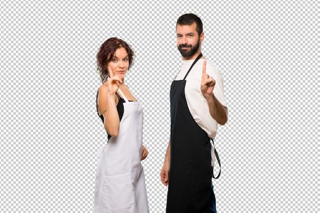最高のサインで指を持ち上げて持ち上げている料理人のカップル