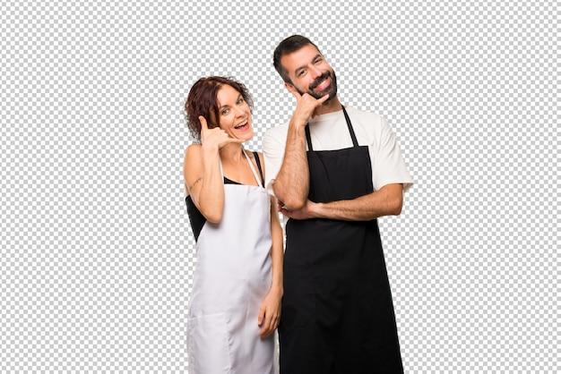 電話のジェスチャーをする料理人のカップル。コールバックバックサイン
