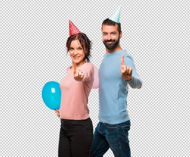 風船と誕生日の帽子とカップルと最高のサインで指を持ち上げる